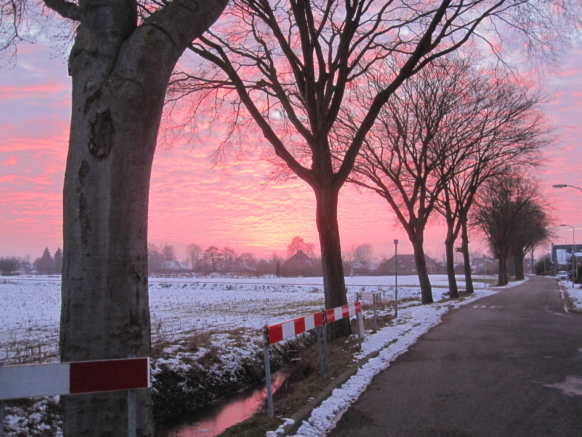 Dutch street with snow and sunset